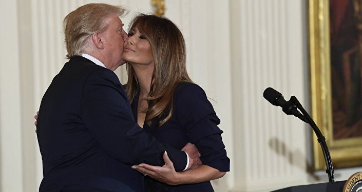 President Donald Trump kisses first lady Melania Trump during a celebration of military mothers and spouses event in the East Room of the White House in Washington, Wednesday, May 9, 2018