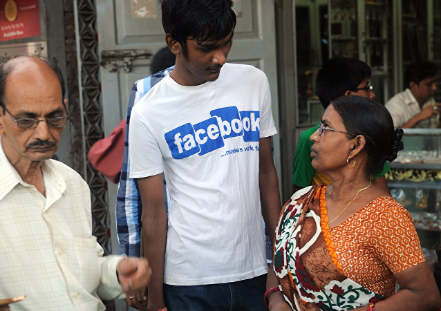 An Indian mother (R) interacts with her son wearing a t-shirt with a Facebook logo at a roadside vegetable market as an officegoer walks past in Mumbai (File)