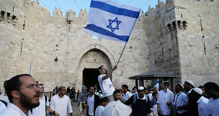 Israelis celebrate as they hold an Israeli flag during a parade marking the annual Jerusalem Day, outside Damascus Gate of Jerusalem's Old City, May 13, 2018