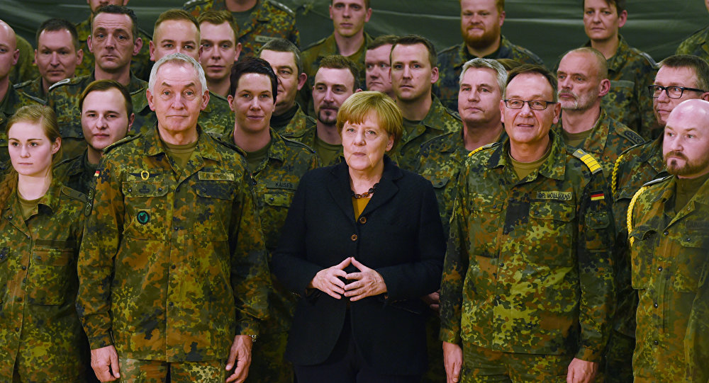 German chancellor Angela Merkel (C) poses next to Surgeon General Michael Tempel (L) and commander Dirk Moellmann (2L) and members of the German army Rapid Medical Response Forces Command in Leer, northern Germany, on December 7, 2015