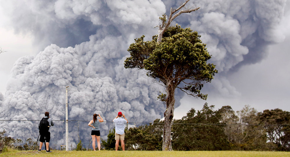 People watch as ash erupts from the Halemaumau crater near the community of Volcano during ongoing eruptions of the Kilauea Volcano in Hawaii, US, May 15, 2018