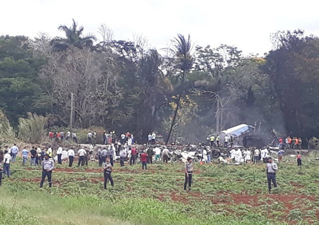 Rescue and search workers on the site where a Cuban airliner with 104 passengers on board plummeted into a yuca field just after takeoff from the international airport in Havana, Cuba, Friday, May 18, 2018.