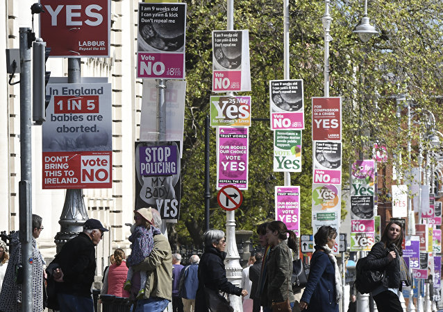 People cross the road past posters urging a yes vote in the referendum to repeal the eighth amendment of the Irish constitution, a subsection that effectively outlaws abortion in most cases, and posters calling for a no vote in the referendum near the government buildings in Dublin on May 12, 2018