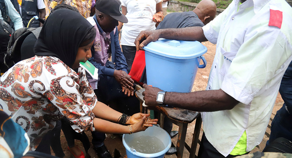 A Congolese health worker instructs residents about washing their hands as a preventive measure against Ebola in Mbandaka Democratic Republic of Congo