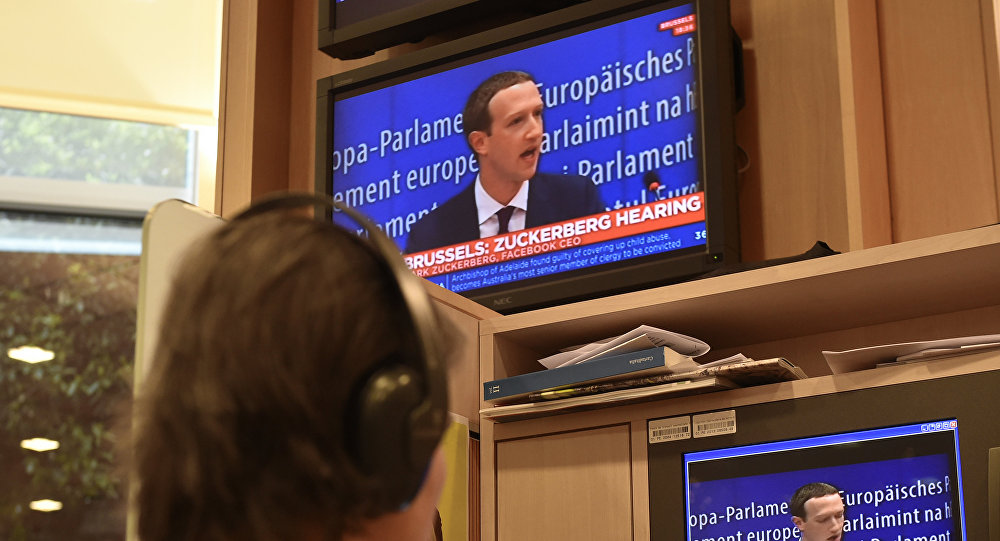 A journalist watches the speech of Facebook CEO Mark Zuckerberg on a television screen, in the press room, during his audition on the data privacy scandal on May 22, 2018 at the European Union headquarters in Brussels
