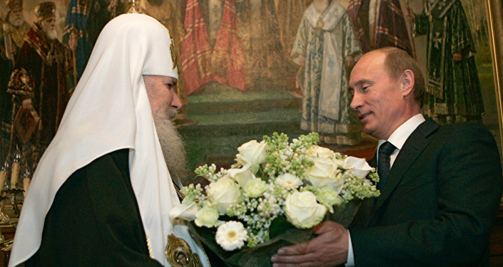 Vladimir Putin presents Patriarch Alexy II with a bouquet of flowers for his birthday.