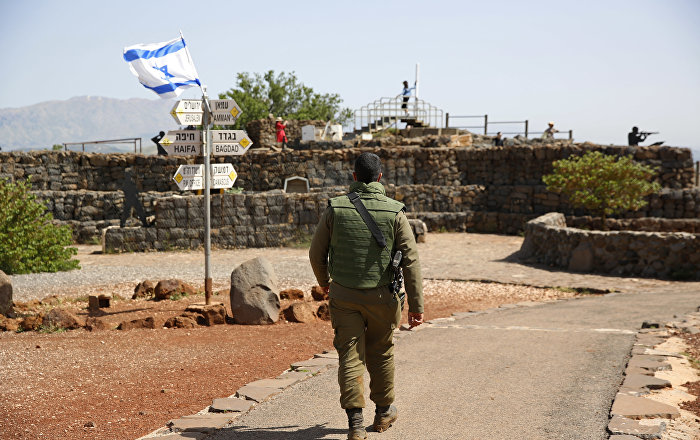 An Israeli soldier walks in an old military outpost, used for visitors to view the Israeli controlled Golan Heights, near the border with Syria, Thursday, May 10, 2018