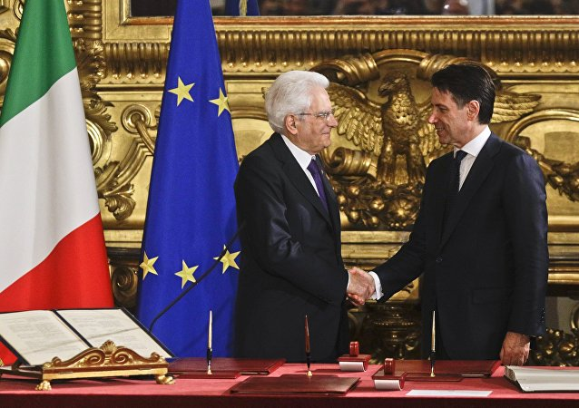 Italian President Sergio Mattarella, left, shakes hands with Premier Giuseppe Conte during the swearing-in ceremony for Italy's new government at Rome's Quirinale Presidential Palace, Friday, June 1, 2018