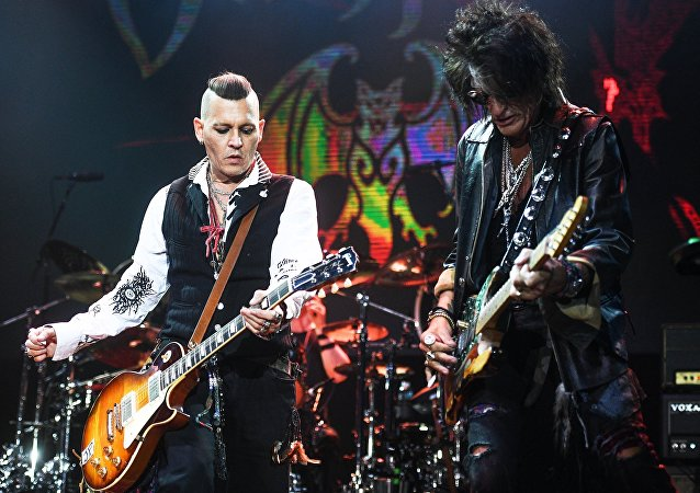 Actor Johnny Depp, left, and Joe Perry, a guitarist of the American rock band Aerosmith, during a performance at the Olimpiysky sports complex