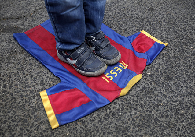 (FILES) In this file photo taken on October 07, 2012, a Palestinian boy steps on a T-shirt of Spanish FC Barcelona football club with the name of it's Argentinian player, Lionel Messi, during a demonstration outside the Spanish consulate in eastern Jerusalem on October 7, 2012 to protest against Barcelona's invitation of Israeli slodier Gilad Shalit to attend today's El Clasico match