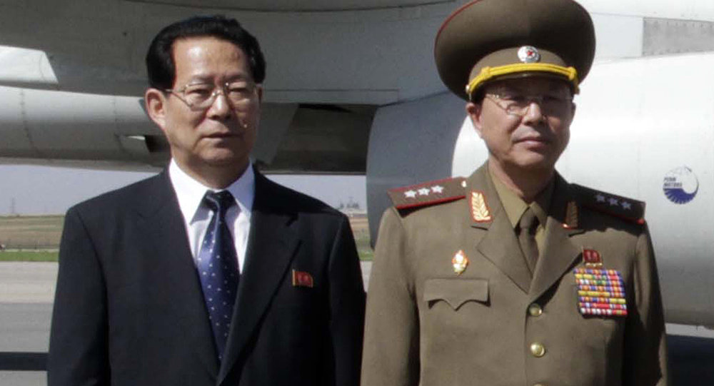 Ri Yong Gil, right, poses at Pyongyang Airport in 2013.