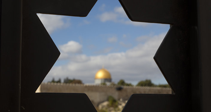 The Dome of the Rock Mosque in the Al-Aqsa Mosque compound in Jerusalem's Old City is seen through a door with the shape of star of David.