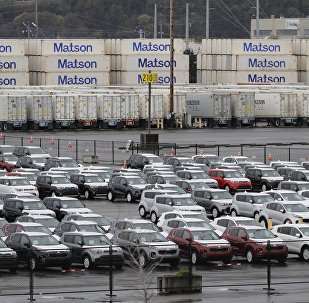 New cars and cargo containers are shown in a staging area, Friday, April 6, 2018, at the Port of Tacoma in Tacoma, Wash.