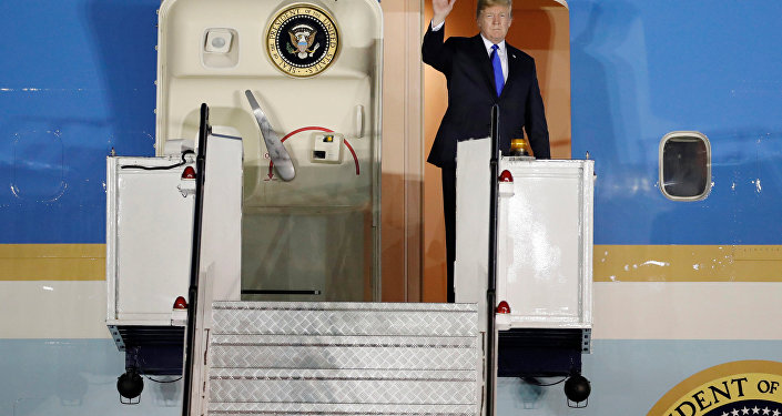 US President Donald Trump waves upon his arrival at Paya Lebar Air Base in Singapore before his summit with North Korean leader Kim Jong Un