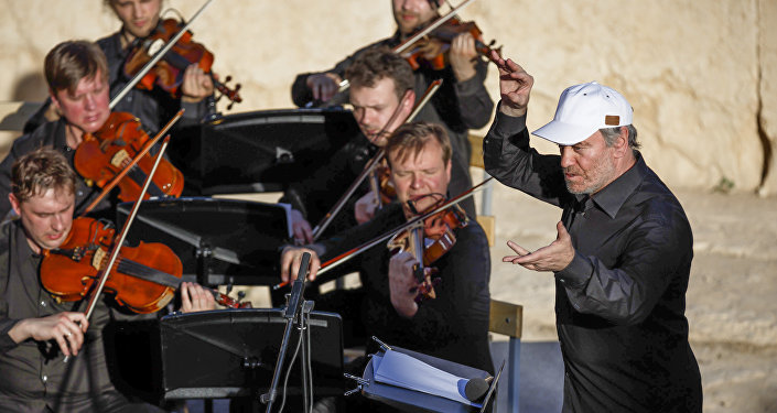 In this Thursday, May 5, 2016 photo provided by Russian Defense Ministry Press Service, the renowned conductor Valery Gergiev, right, leads a performance by the Mariinsky Symphony Orchestra from St. Petersburg, during the concert at the UNESCO world heritage site of Palmyra, the central city of Homs, Syria