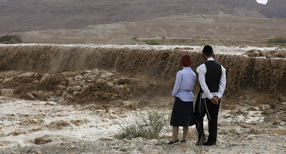 (File) Ultra-orthodox Jews watch flooded water running through a valley blocking the main road along the Dead Sea in the Judean desert, near the desert fortress of Masada north of Ein Bokek, following heavy rainfall in the mountains on April 25, 2018