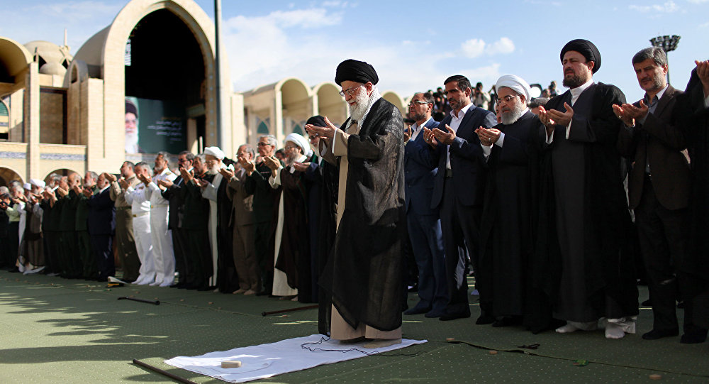 A handout picture released by the official website of the Iranian supreme leader shows Ayatollah Ali Khamenei (L) leading the Eid al-Fitr prayers at the Imam Khomeini grand mosque in the capital Tehran on June 15, 2018