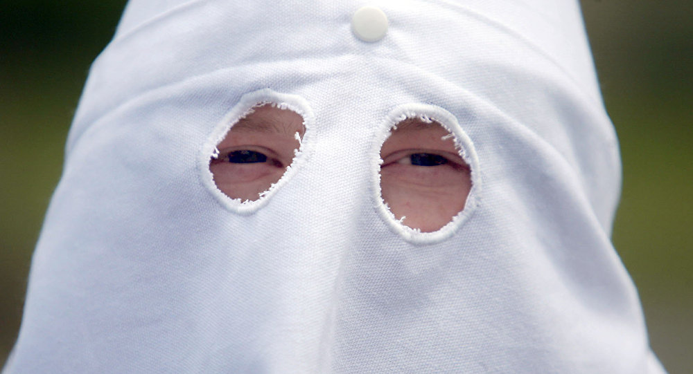 An unidentified member of the Ku Klux Klan peers from beneath a hooded mask at a Ku Klux Klan rally Saturday, June 10, 2006