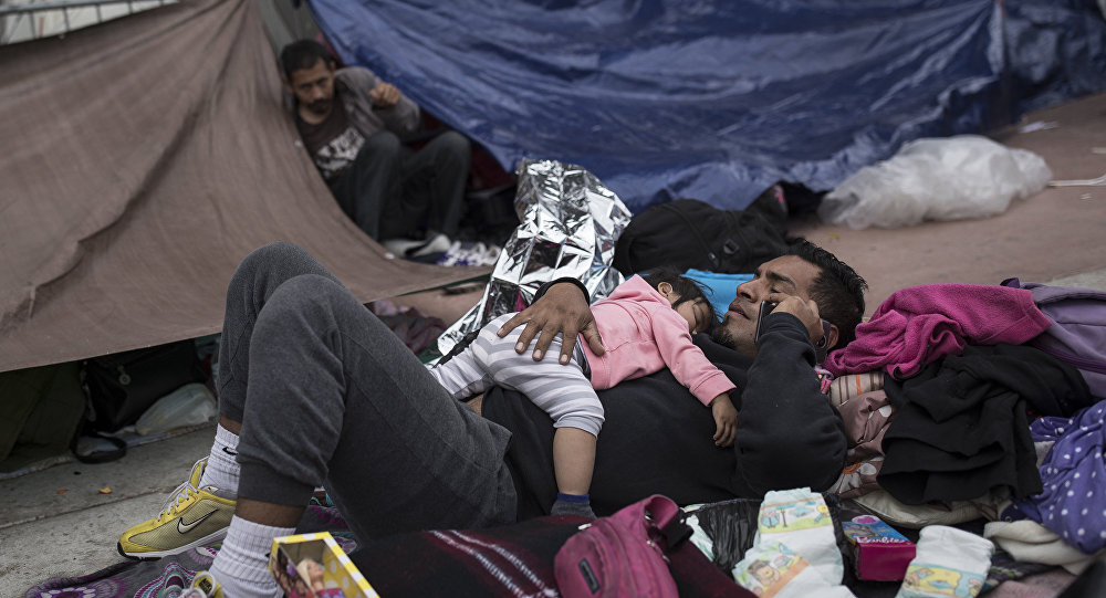 A migrant father and child rest outside the El Chaparral port of entry building at the US-Mexico border in Tijuana, Mexico