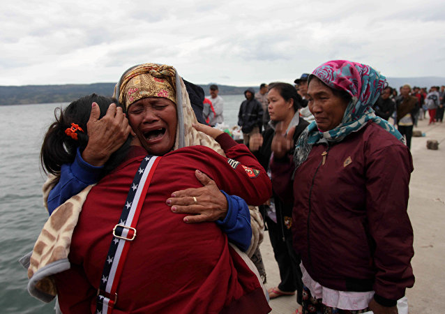 Relatives cry while waiting for news on missing family members who were on a ferry that sank yesterday in Lake Toba, at Tigaras Port, Simalungun, North Sumatra, Indonesia June 19, 2018