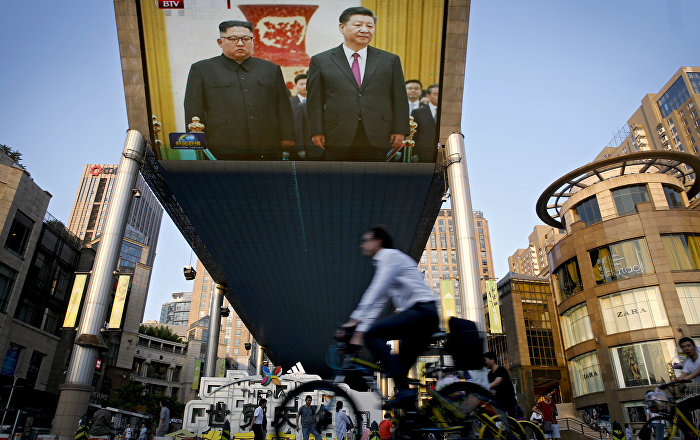 People bicycle past a giant TV screen broadcasting the meeting of North Korean leader Kim Jong Un and Chinese President Xi Jinping during a welcome ceremony at the Great Hall of the People in Beijing, Tuesday, June 19, 2018