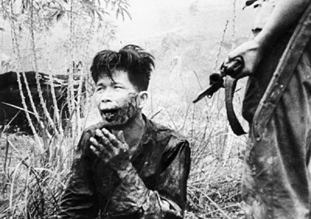 A wounded terrorist being held at gunpoint after his capture, in Malaya