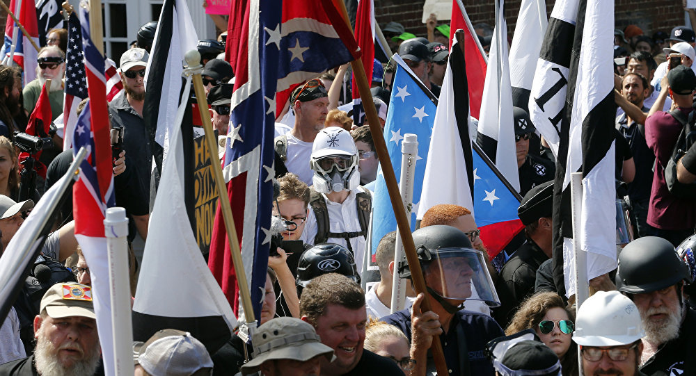 In this Saturday, Aug. 12, 2017, file photo, white nationalist demonstrators walk into the entrance of Lee Park surrounded by counter demonstrators in Charlottesville, Va.