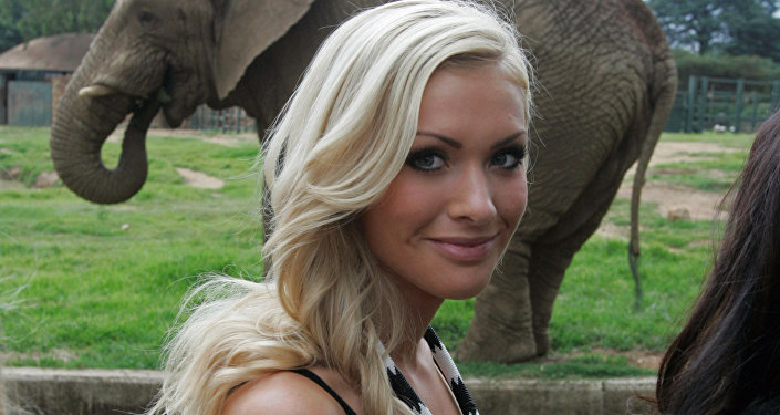(File) Miss World participant Miss Iceland, Alexandra Helga Ivarsdottir stands in front of a elephant during a visit to the Zoo, inJohannesburg, South Africa, Saturday, Dec. 6, 2008