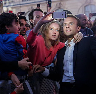 French President Emmanuel Macron poses for a selfie with guests during the 'Fete de la Musique', the music day celebration, in the courtyard of the Elysee Palace, in Paris, France, June 21, 2018