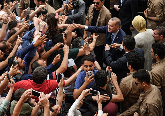 Turkey's President Recep Tayyip Erdogan, leader of the Justice and Development Party (AKP) and his wife Emine are greeted by supporters as they leave the polling station after casting their votes during snap twin Turkish presidential and parliamentary elections in Istanbul on June 24, 2018