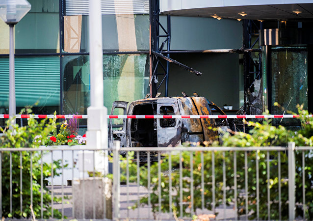 A van is seen burned out after crashing into the glass facade of the head office of Dutch newspaper De Telegraaf in what police said was a deliberate action in Amsterdam, Netherlands June 26, 2018