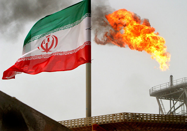 A gas flare on an oil production platform in the Soroush oil fields is seen alongside an Iranian flag in the Persian Gulf, Iran, July 25, 2005