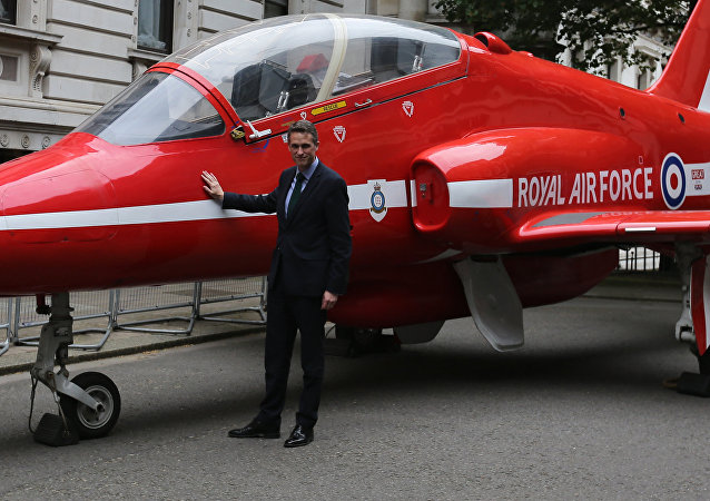 Britain's Defence Secretary Gavin Williamson poses alongside a replica British Royal Air Force's (RAF) Red Arrows BAE Hawk aircraft outside numbers 10 and 11 Downing Street in central London on May 23, 2018, as part of the RAF's 2018 centenary celebrations