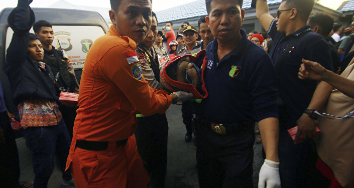 An Indonesian rescue team carry a victim of a capsized boat at Paotere port in Makassar, South Sulawesi , Indonesia, Wednesday, June 13, 2018