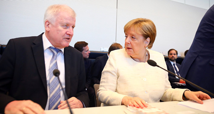 German Chancellor Angela Merkel and Interior Minister Horst Seehofer arrive for a CDU/CSU fraction meeting in Berlin, Germany, July 3, 2018