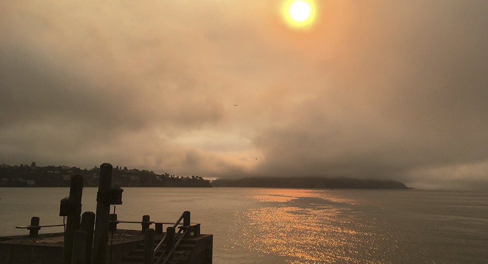 In this photo taken Sunday, July 1, 2018, a haze from wildfires is seen over Angel Island, at right, and San Francisco Bay from Sausalito, Calif. A fire official says a massive wildfire tearing through rural Northern California is burning 1.5 square miles (4 square kilometers) of rugged terrain an hour. Gabe Lauderbale, a spokesman with the California Department of Forestry and Fire Protection, said Monday, that hot temperatures and gusty winds are contributing to the fast spread of the blaze in sparsely populated areas of Yolo and Napa counties