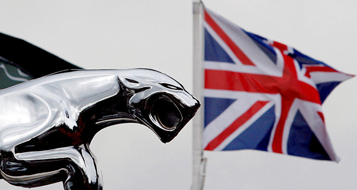 A Union flag is seen behind a Jaguar car emblem outside a dealership in Manchester, England