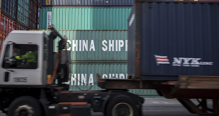 In this Thursday, July, 5, 2018 photo, a jockey truck passes a stack of 40-foot China Shipping containers at the Port of Savannah in Savannah, Ga.
