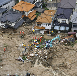 Rescue workers are seen next to houses damaged by a landslide following heavy rain in Hiroshima, western Japan, in this photo taken by Kyodo July 7, 2018