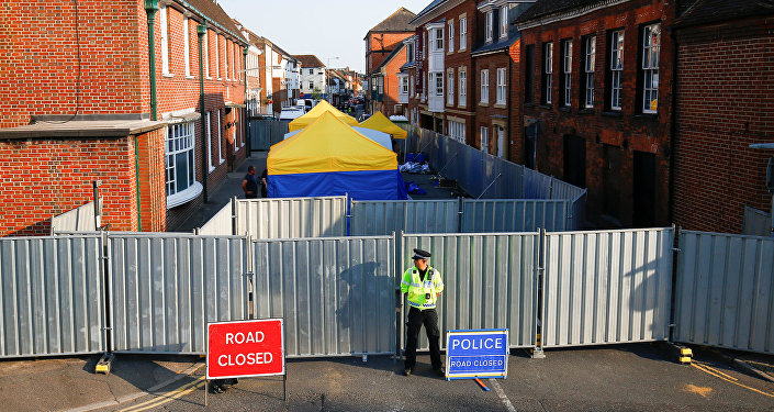 A police officer stands in front of screening erected behind John Baker House as forensic tents are erected, after it was confirmed that two people had been poisoned with the nerve-agent Novichok, in Amesbury, Britain