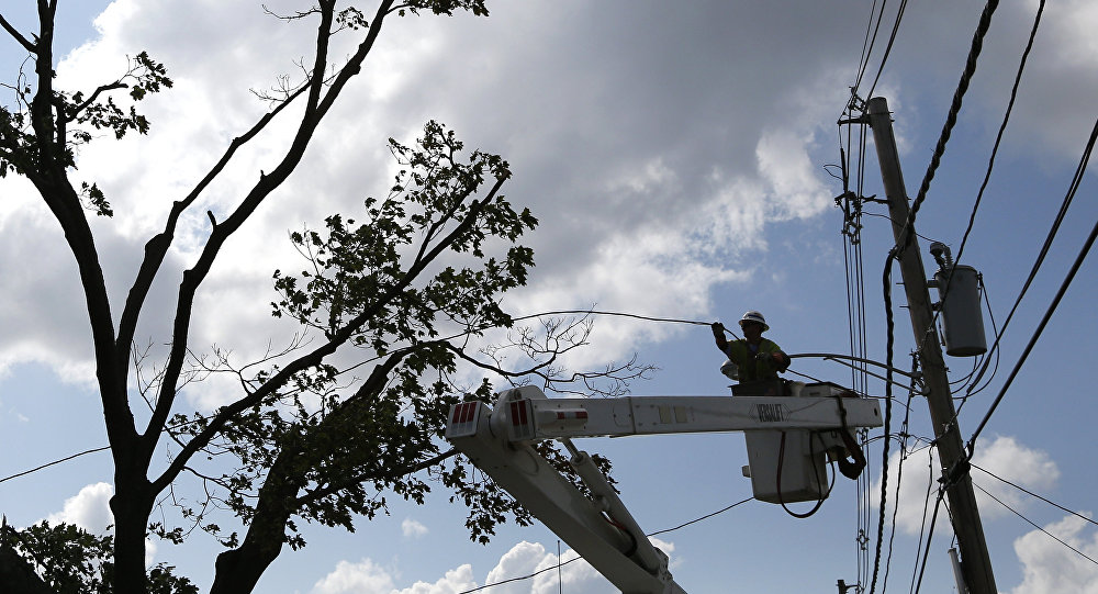 A National Grid crew member works to restore power on lines in Revere, Mass. Monday, July 28, 2014, after a tornado touched down