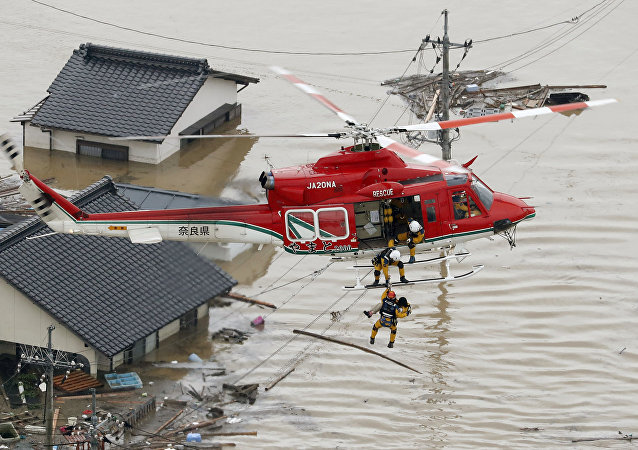 An aerial view shows a local resident being rescued from a submerged house by rescue workers using helicopter at a flooded area in Kurashiki, southern Japan, in this photo taken by Kyodo July 7, 2018