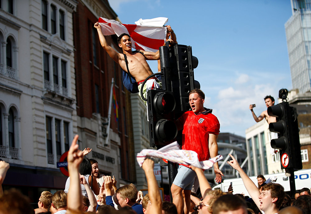 Soccer Football - World Cup - England fans watch Sweden vs England - London, Britain - July 7, 2018 England fans celebrate by climbing traffic lights after the match