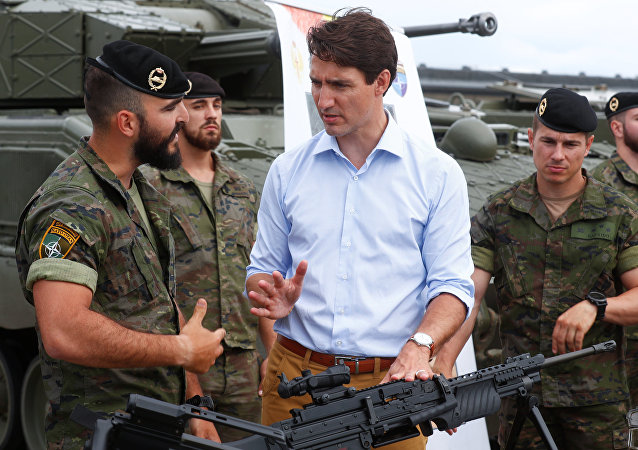Canada's Prime Minister Justin Trudeau speaks with Spanish soldiers as he visits NATO eFP Canadian-led battlegroup troops in Adazi military base, Latvia July 10, 2018