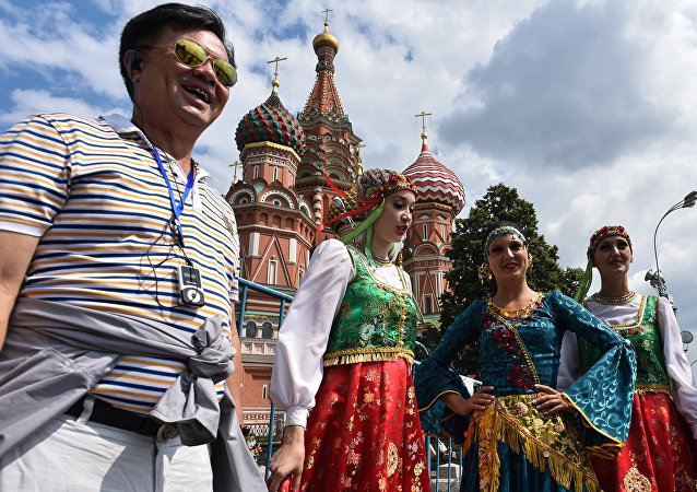 A tourist poses for a picture next to women wearing traditional dresses at Moscow's Red Square on July 10, 2015