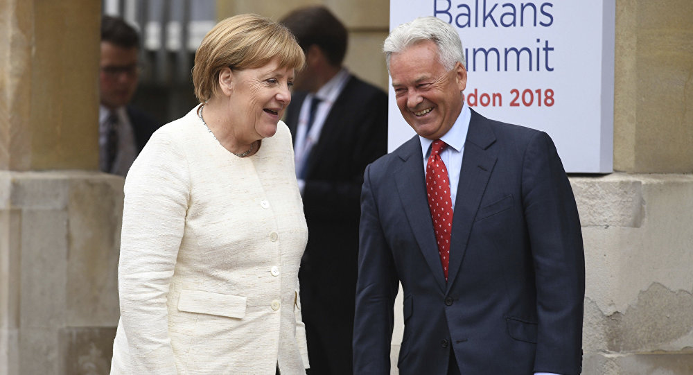 Britain's Minister of State for Europe and the Americas Alan Duncan, right, greets German Chancellor Angela Merkel outside Lancaster House in London, during the second day of the Western Balkans summit, Tuesday July 10, 2018.