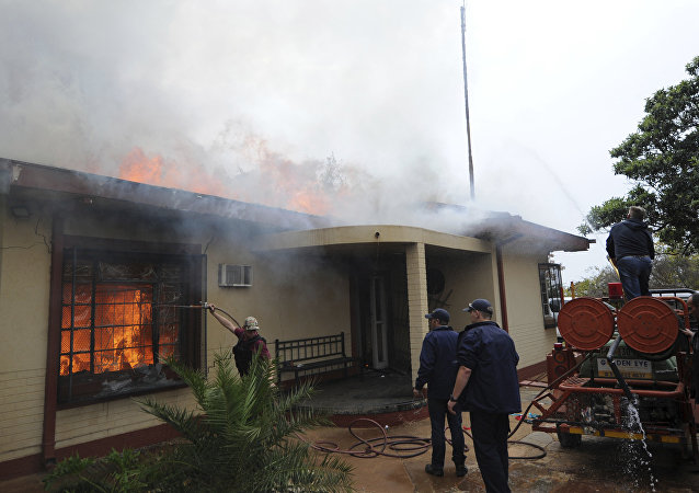 Firemen attempt to extinguish s fire at a white residence in Coligny, South Africa, in the town where two South Africa white farmers were released on bail by the magistrates court, Monday May 8, 2017. The two, who are accused of murdering a black teenager, were granted bail in the racially sensitive case that sparked racial violence.
