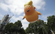 A six-meter high cartoon baby blimp of U.S. President Donald Trump is flown as a protest against his visit, in Parliament Square in London, England, Friday, July 13, 2018