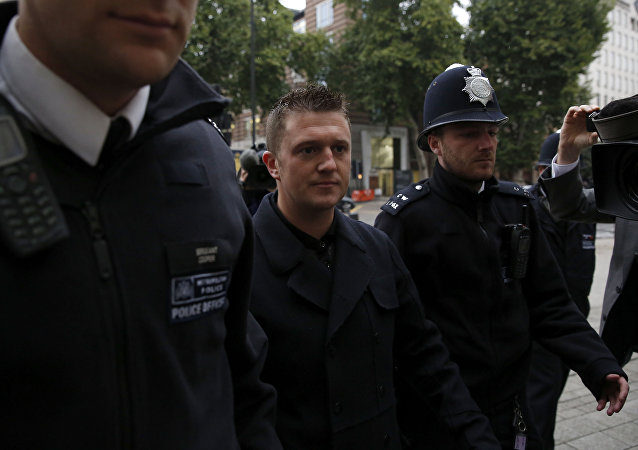 Tommy Robinson the former leader of the far-right EDL English Defence League group is flanked by police officers as he arrives for an appearance at Westminster Magistrates Court in London, Wednesday, Oct. 16, 2013