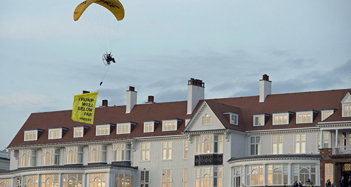 In this Friday, July 13, 2018 photo, a Greenpeace protester flying a microlight passes over US President's Donald Trump's resort in Turnberry, South Ayrshire, Scotland with a banner reading Trump: Well Below Par, shortly after the US President arrived at the hotel. Scottish police said the protester breached a no-fly zone over Turnberry hotel and committed a criminal offence.
